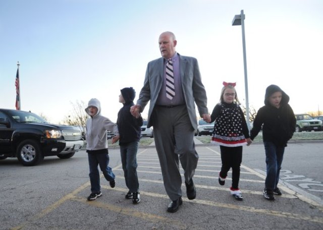 Nellie Doneva/Reporter-News Heath Burns, Abilene Independent School District superintendent, takes his two sets of twin children, Eli and Emma, 8, and Gabe and Grant, 6, to school at Thomas Elementary School